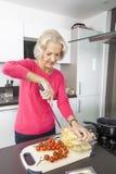 Senior woman preparing food at kitchen counter Royalty Free Stock Image