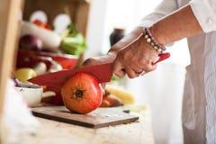 Senior woman preparing fruit salad stock photo