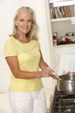 Senior Woman Preparing Meal At Cooker Royalty Free Stock Images