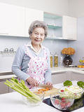 Senior woman preparing meal in kitchen Royalty Free Stock Photos