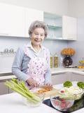 Senior woman preparing meal in kitchen Royalty Free Stock Photos