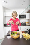 Senior woman preparing salad at kitchen counter Royalty Free Stock Images