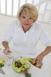 Senior woman preparing vegetable salad Royalty Free Stock Photo