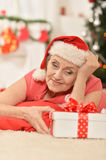Senior woman with present. Portrait of smiling  senior woman in Santa hat with Christmas present Stock Photography