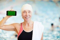 Senior Woman Presenting Smartphone in Pool royalty free stock photos