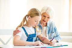 Senior woman and preteen girl drawing together at table Royalty Free Stock Photography