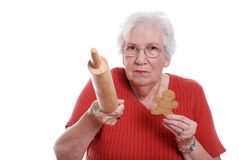 Senior woman protecting gingerbread men cookies Royalty Free Stock Image