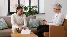 Senior woman psychologist and sad man patient stock footage