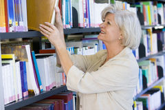 Senior woman pulling a library book off shelf Stock Photos