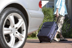 Senior woman pulling suitcase on wheels from parked car boot on driveway, rear view (surface level) Royalty Free Stock Photo