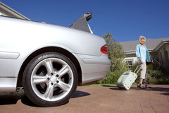 Senior woman pulling suitcase on wheels from parked car boot on driveway, smiling, side view, portrait (surface level) Royalty Free Stock Photography