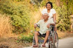 Senior woman pushing her disabled husband on wheelchair Royalty Free Stock Photo