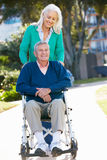 Senior Woman Pushing Husband In Wheelchair Stock Image