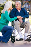 Senior Woman Pushing Husband In Wheelchair Stock Photography
