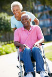 Senior Woman Pushing Husband In Wheelchair Royalty Free Stock Photography