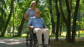 Senior woman pushing husband in wheelchair outside stock footage
