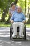 Senior woman pushing husband in wheelchair Royalty Free Stock Images
