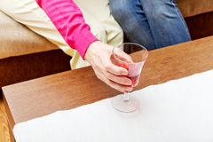 Senior woman put glass of wine on table Royalty Free Stock Image