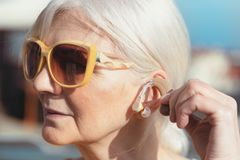 Senior woman puts on the hearing aid. Deafness, senior health care concept stock photography