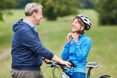 Senior Woman Puts On A Bicycle Helmet Royalty Free Stock Photos