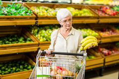 Senior woman putting banana in her trolley Royalty Free Stock Photo
