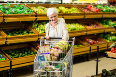Senior woman putting banana in her trolley Royalty Free Stock Image