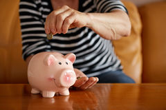 Senior woman putting coin into piggy bank Stock Photos