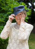 Senior woman putting on her hat Stock Photo