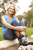 Senior Woman Putting On In Line Skates In Park. Smiling To Camera Stock Photos