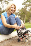 Senior Woman Putting On In Line Skates In Park stock images