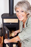 Senior woman putting logs in the woodburner. Senior woman putting logs into the woodburner stove at home to heat the house during winter looking back at the Stock Photo