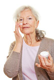 Senior woman putting lotion on her Stock Images