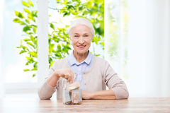 Senior woman putting money into glass jar at home. Savings, annuity insurance and people concept - smiling senior woman putting money into glass jar at home over royalty free stock photo
