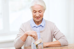 Senior woman putting money into glass jar at home. Savings, money, annuity insurance, retirement and people concept - smiling senior woman putting bank notes royalty free stock photo