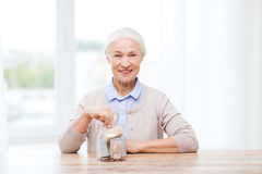 Senior woman putting money into glass jar at home Royalty Free Stock Photography