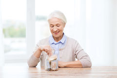 Senior woman putting money into glass jar at home. Savings, money, annuity insurance, retirement and people concept - smiling senior woman putting bank notes royalty free stock photography