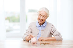 Senior woman putting money to piggy bank at home Stock Photos