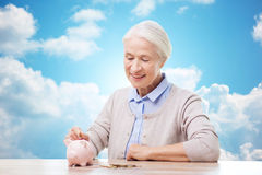 Senior woman putting money to piggy bank Stock Photo