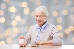 Senior woman putting money to piggy bank Royalty Free Stock Photo