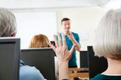 Senior Woman Raising Hand In Computer Class. Senior women raising hand while tutor explaining in computer class Stock Image