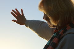 Senior woman reaching out to the sun Stock Photo