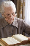 Senior woman reading. Senior woman in glasses reading old Bible Stock Photography