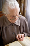 Senior woman reading. Senior woman in glasses reading old Bible Stock Image