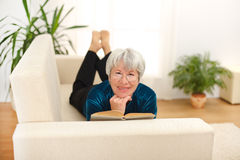 Senior woman reading. Senior woman laying on sofa and reading book Stock Images