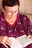 Senior woman reading. Close up of senior woman sitting on sofa and reading book Stock Photography