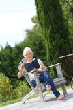 Senior woman reading in backyard royalty free stock image