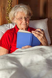 Senior woman reading in bed Stock Images