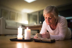 Senior woman reading Bible. Burning candles next to her. Beautiful senior woman at home in her living room lying on the floor reading her Bible. Burning candles Royalty Free Stock Photography