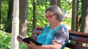 Senior woman reading bible in the park stock footage