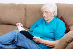 Senior woman reading a book. While relaxing on the couch Royalty Free Stock Images